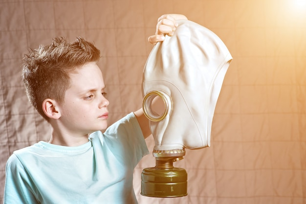 Portrait of a boy in a light t-shirt with a gas mask