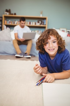 Portrait of boy lying on floor while father working