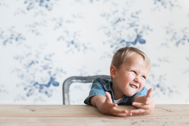 Portrait of a boy making funny face sitting in front of wallpaper