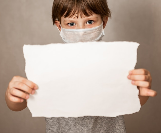 Portrait of boy in a mask respirator holds a blank sheet of paper