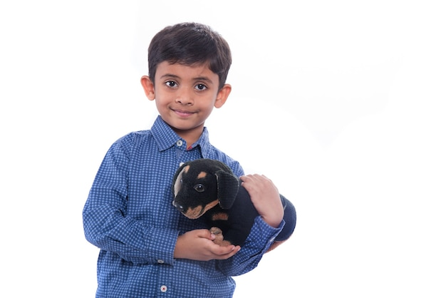 Portrait of boy playing with his stuffed animal pet on white wall