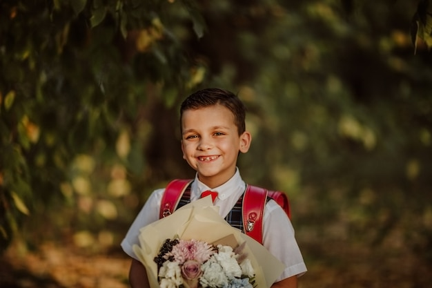 Portrait of a boy in school uniform holding a bunch of flowers in a park