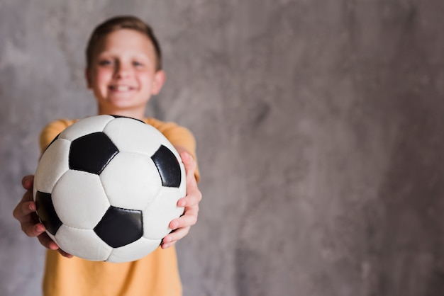 Portrait of a boy showing soccer ball toward camera standing front of concrete wall