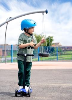 Мальчик портрета показывая большие пальцы руки вверх пока стоящ на самокате в спортивной площадке.