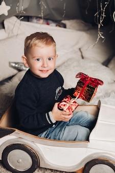 肖像画の少年はギフトとクリスマスボックスを示しています