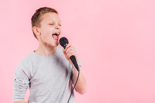 Portrait of a boy singing song on microphone against pink background