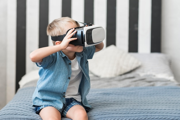 Portrait of a boy sitting on bed wearing virtual reality goggles