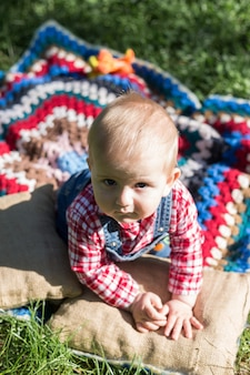 Portrait of a boy sitting on a blanket on a fresh grass in a city park in summer