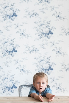 Portrait of a boy sitting on chair against wallpaper