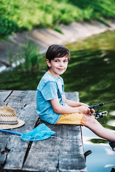 Portrait of boy sitting on pier fishing on lake