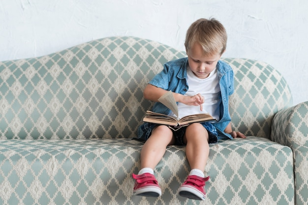 Portrait of a boy sitting on sofa pointing finger over book