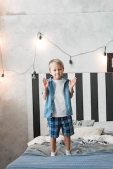 Portrait of a boy standing on bed with illuminated light on wall