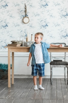 Portrait of a boy standing near the table in the living room