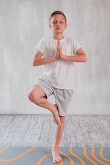 Portrait of a boy standing in yoga pose on one leg