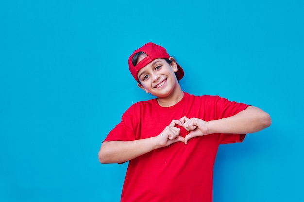 A portrait of boy in t-shirt and red cap making a heart with his hands