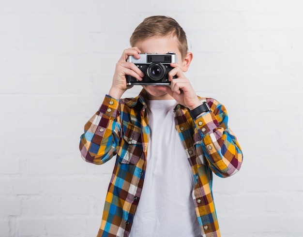 Portrait of a boy taking picture from an old vintage camera against white brick wall