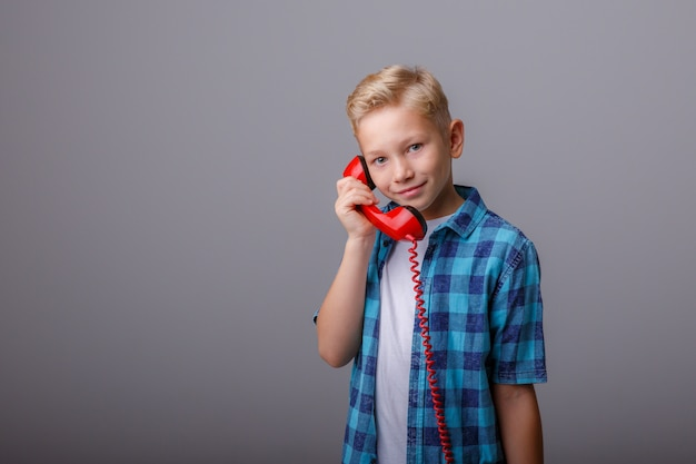 Portrait of a boy talking to an old phone