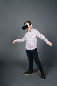 Portrait of a boy using virtual reality glasses standing against gray background