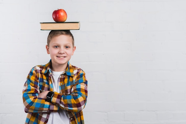 Portrait of a boy with arms crossed balancing apple and book on head against white background