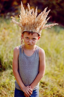 Portrait boy with a crown on the head and a sword in hands.