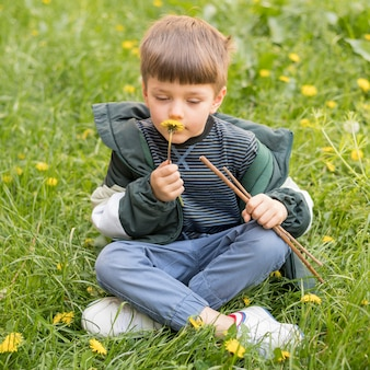 Portrait boy with dandelion playing