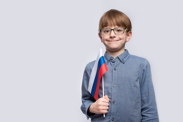 Portrait of boy with flag of russia in hands on white studio