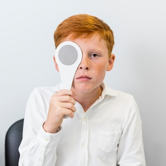 Portrait of boy with freckle holding occluder in front of his eye