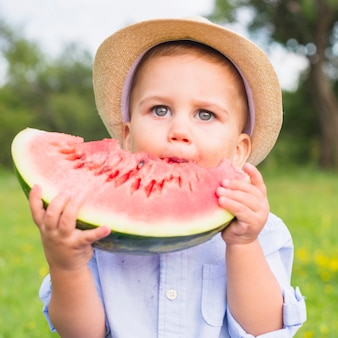 Portrait of a boy with gray eyes eating watermelon