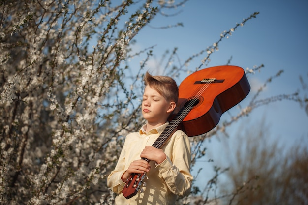 Portrait boy with guitar standing near blooming flowers in summer day.