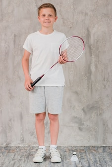 Portrait of a boy with racket and shuttlecock standing in front of concrete wall