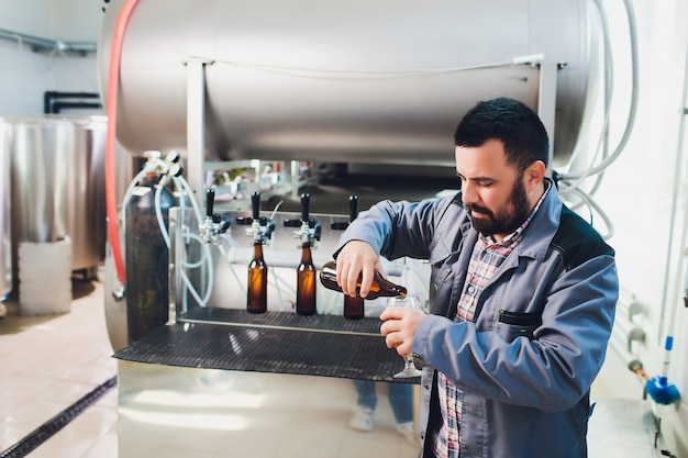 Portrait of brewer making beer on his workplace in the brew-house