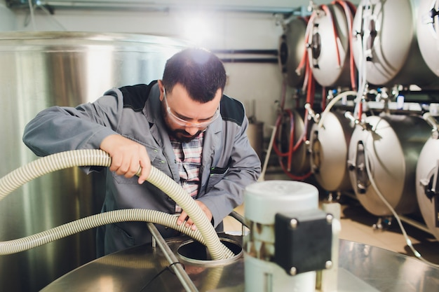 Portrait of brewer who is making beer on his workplace in the brew-house..
