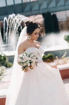 Portrait of the bride in the city near the fountain.a stunning young bride with curly hair . wedding day. . beautiful portrait of the bride without the groom.