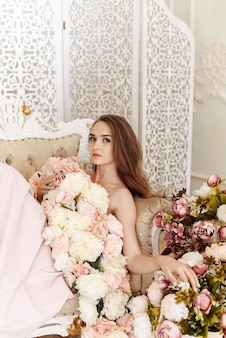 Portrait of a bride girl in an elegant dress of roses, peonies and flowers