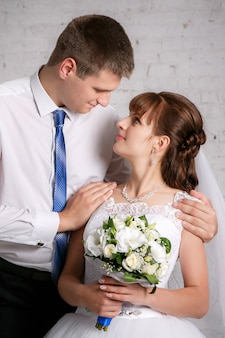 Portrait of the bride and groom on the white brick wall background