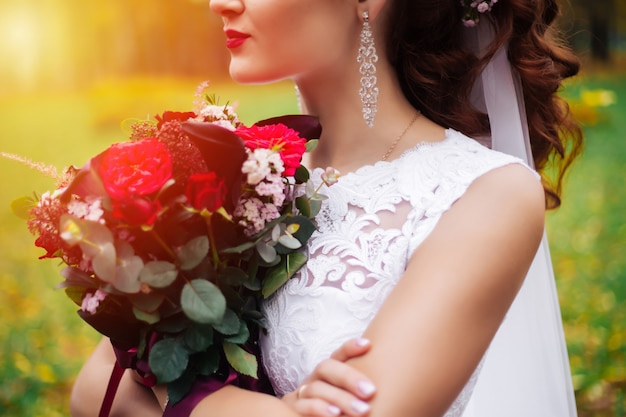 Portrait of bride with a bouquet of flowers in the park, all-sunny day