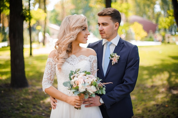 Portrait of a bridegroom embracing a blonde bride