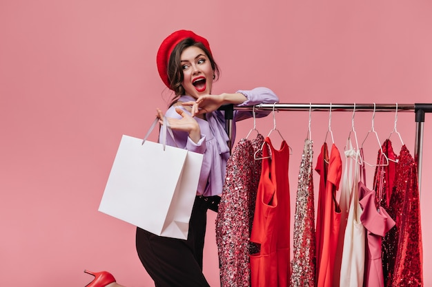 Ritratto di brillante signora con rossetto rosso in posa felicemente con il pacchetto durante lo shopping su sfondo rosa.