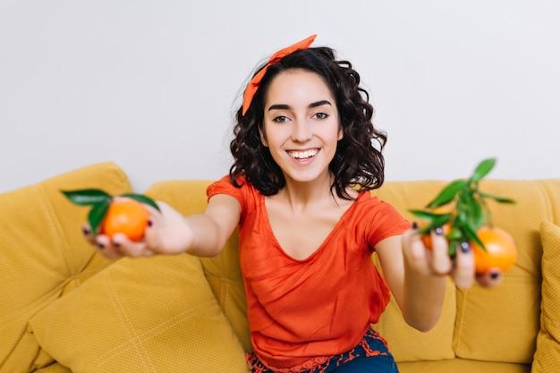 モダンなアパートメントのソファでみかんを浮かべて興奮してうれしそうな若い女性の肖像画明るい真の肯定的な感情。楽しみ、喜び、積極性を表現する