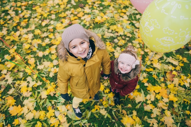 Portrait of a brother and sister in an autumn park, top view