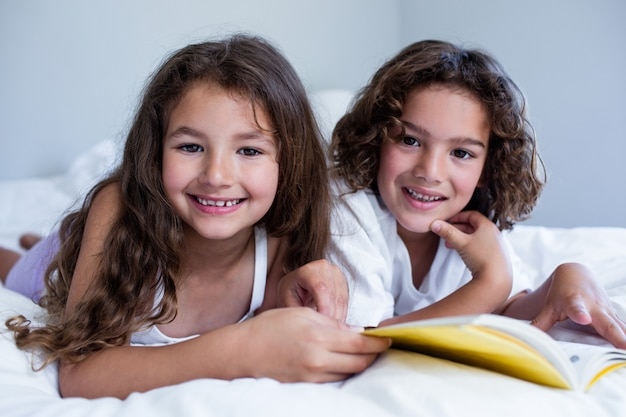 Portrait of brother and sister reading book together on bed