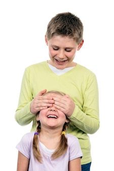 Portrait of brother and sister with hand on eyes