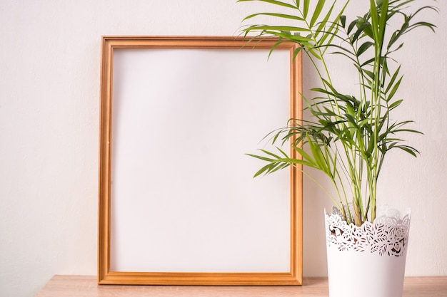 木製のテーブルの上の肖像画額縁モックアップ。白い壁の背景。スカンジナビアのインテリア。