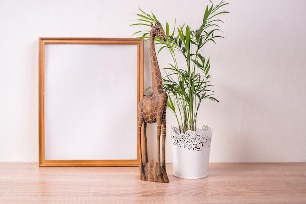 木製のテーブルの上の肖像画額縁モックアップ。木製の装飾キリンフィギュアと手のひら。白い壁の背景。スカンジナビアのインテリア。