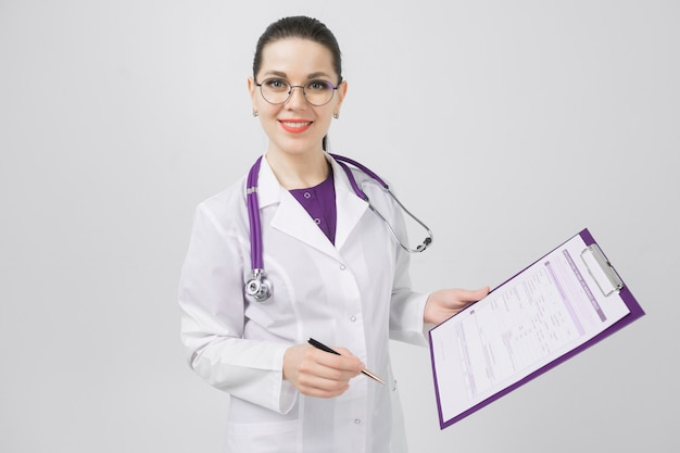 Portrait of brunet in doctors costume with folder in her hands on background