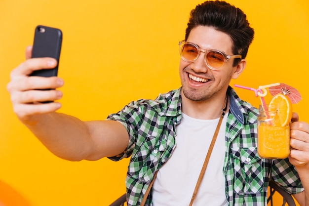 Portrait of brunet man in orange sunglasses holding cocktail glass and taking selfie on orange space.