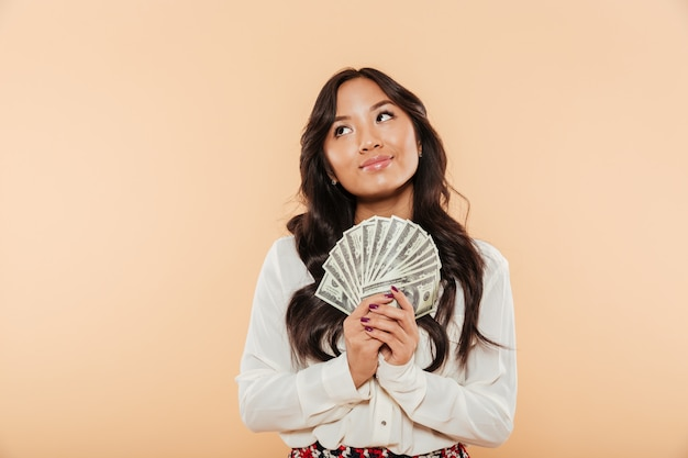 Portrait of brunette asian female looking up while holding fan of 100 dollar bills being successful businesswoman over peach background