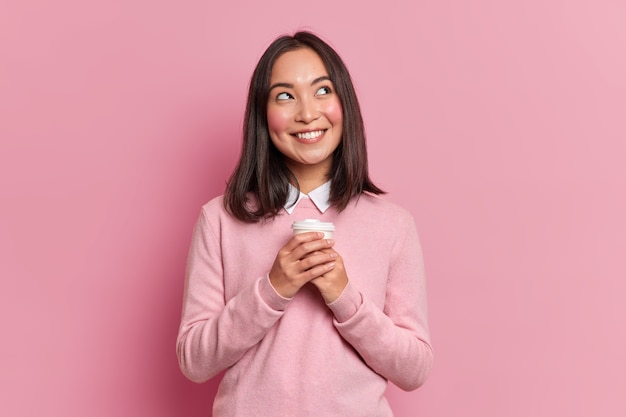 Portrait of brunette asian woman with dreamy expression smiles pleasantly daydreams with takeaway coffee wears neat pink jumper poses indoor. pensive female model feels good