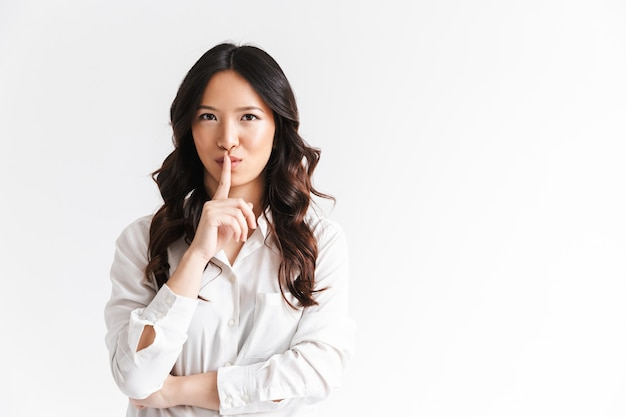 Portrait of brunette asian woman with long black hair holding index finger on lips and asking to keep quiet