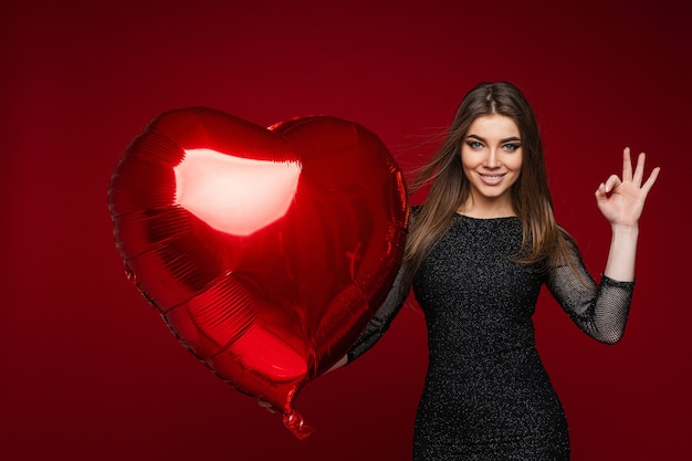 Portrait of brunette caucasian woman in dark cocktail dress with red heart-shaped balloon making okay gesture with hand. isolate on red background.